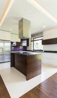 Open space in home with wooden kitchen island, fridge and cupboards